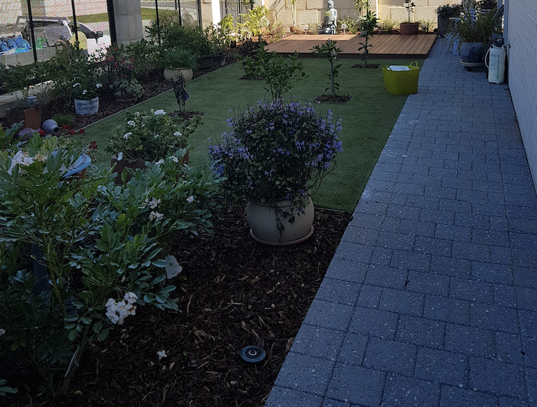A small garden with sa deck out the front of a house.